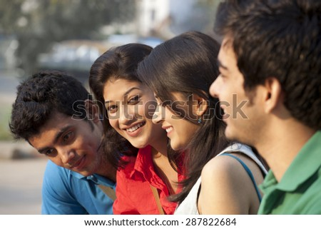 Group of happy students sitting together - stock photo