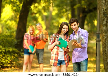 group of happy students with books in the Park on a Sunny day. - stock photo