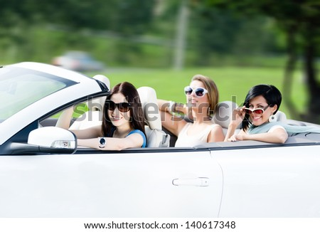 Group of happy teenagers driving the cabriolet. Adorable car trip on vacation - stock photo