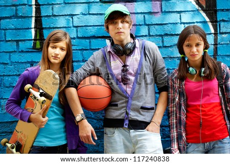 Group of happy teens by painted wall looking at camera - stock photo