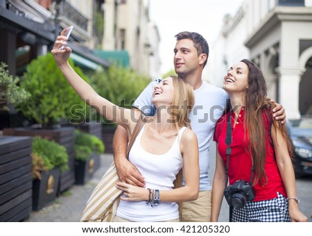 Group of happy tourists friends laughing and taking a selfie in the street