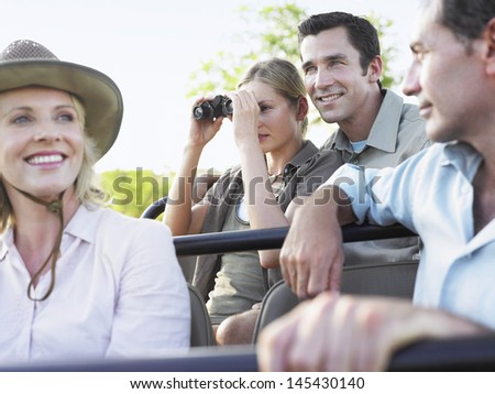 Group of happy tourists on safari sitting in jeep - stock photo