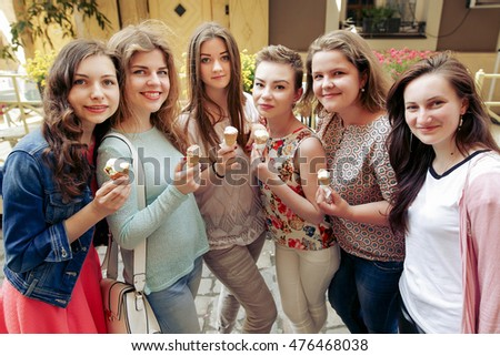 Group of happy women holding ice-cream in hands and having fun, partying in city street, joyful moments