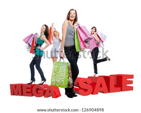 Group of happy women with shopping bags isolated on white. Girls standing on 3 dimensional text. - stock photo