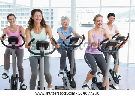 Group of happy women working out at class in gym