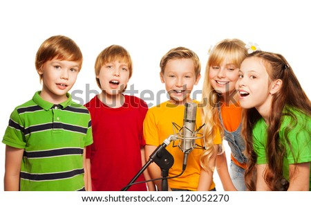 Group of 5 happy 8 years old kids with microphone singing together - stock photo