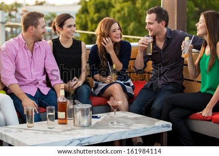 Group of happy young adults having drinks and talking at a terrace - stock photo