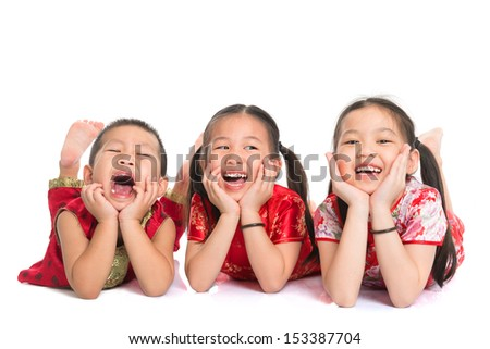 Group of happy young Asian children in traditional Cheongsam dress lying on floor with head on hands, isolated on white background - stock photo