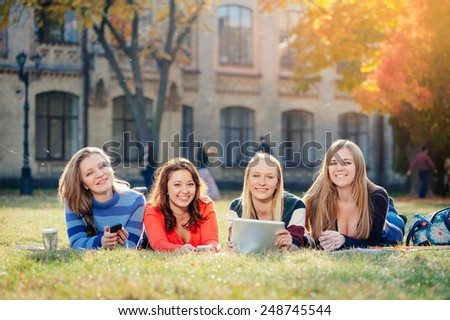 Group of happy young female college students smiling lying on the grass in the campus - stock photo