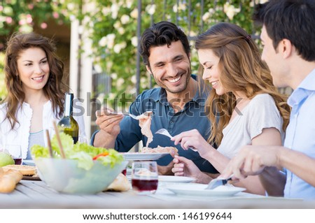 Group Of Happy Young Friends Having Dinner At Patio - stock photo