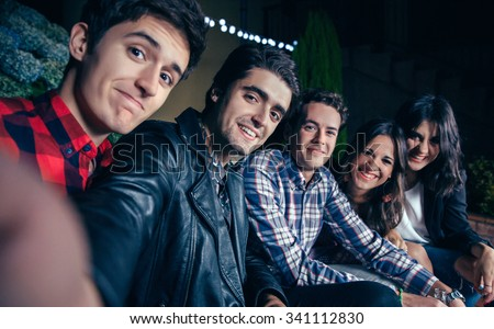 Group of happy young friends smiling while taking a selfie photo in a outdoors party. Friendship and celebrations concept. - stock photo