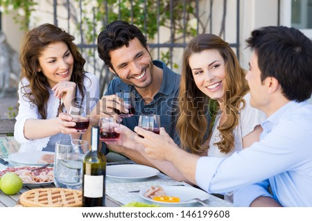 Group Of Happy Young Friends Toasting Wine Glass Outdoor While Having Lunch - stock photo