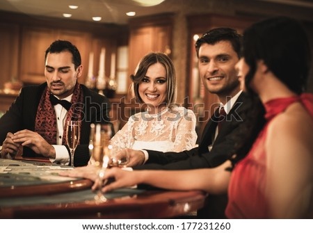 Group of happy young people behind gambling table with drinks - stock photo