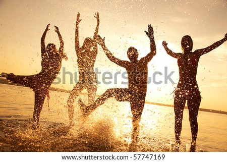 group of happy young people dancing and spraying at the beach on  beautiful summer sunset - stock photo