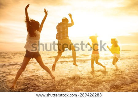 group of happy young people dancing on the beach