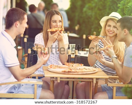 Group of happy young people eating pizza in a restaurant