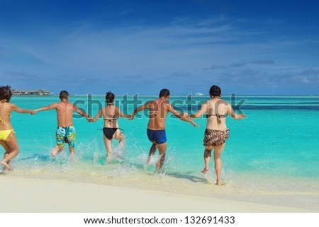 group of happy young people have fun and joy at the  white sand  beach on beautiful summer  day