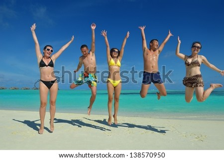 group of happy young people have fun and joy at the  white sand  beach on beautiful summer  day - stock photo