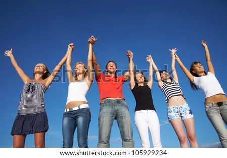 group of happy young people holding hands raised together in the sky - stock photo