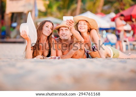 Group of happy young people in bathing suits enjoying sunset on the beach and taking selfie picture, self photo during joyful holidays - stock photo