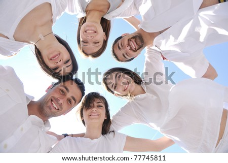 Group of happy young people in circle at beach  have fun and smile