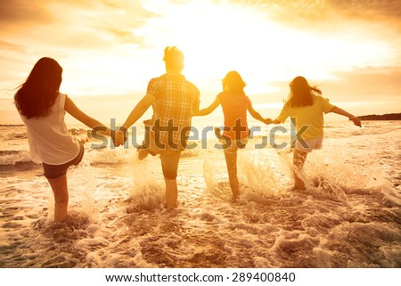 group of happy young people playing on the beach - stock photo