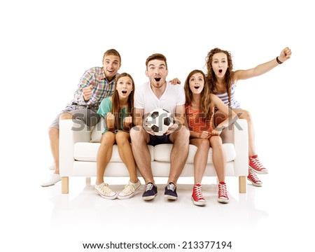 Group of happy young people sitting on sofa and holding soccer ball, isolated on white background. Best friends - stock photo