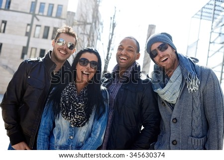 Group of happy young people standing in the springtime sunlight, wearing sunglasses, laughing.