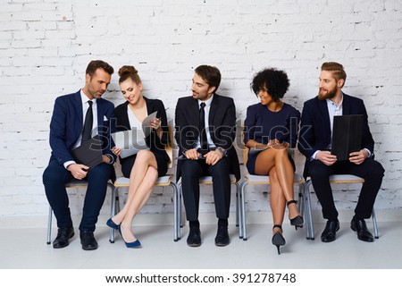 Group of happy young people waiting for job interview - stock photo
