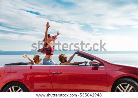 Group of happy young people waving from the red convertible.