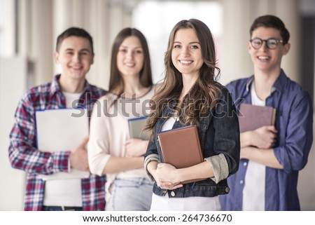 Group of happy young students in a university. - stock photo