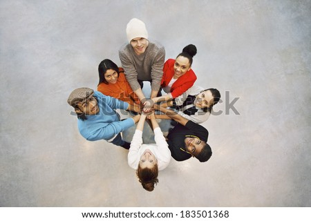 Group of happy young students showing. Top view of multiethnic group of young people putting their hands together. Young students standing in a circle making stack of hands showing unity as a team. - stock photo
