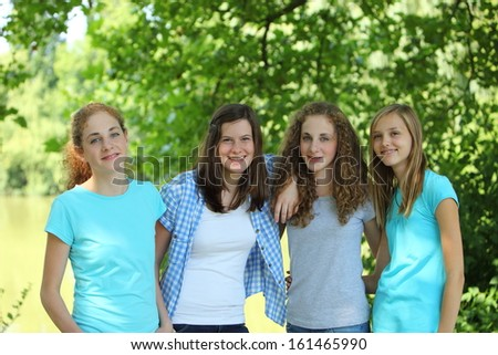 Group of happy young teenage girls standing arm in arm in the park on a sunny day during the summer vacation
