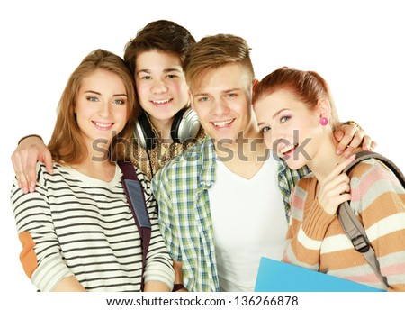 Group of happy young teenager students standing and smiling with books and bags - stock photo