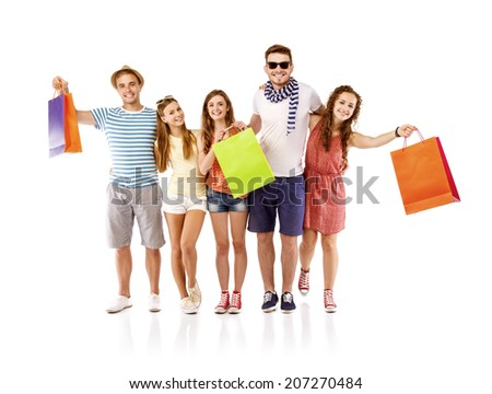 Group of happy young teenager students standing and smiling with shopping bags isolated on white background. - stock photo