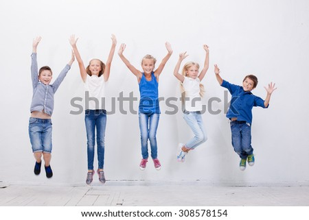 Group of happy young teens jumping over a white background - stock photo