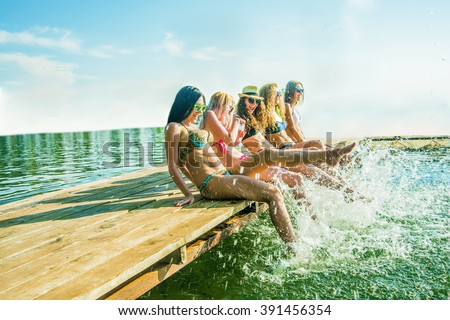 group of happy young woman feet splash water in sea and spraying at the beach on beautiful summer sunset light. Five sexy girls playing on wooden pontoon against blue sky background. Enjoy holiday - stock photo