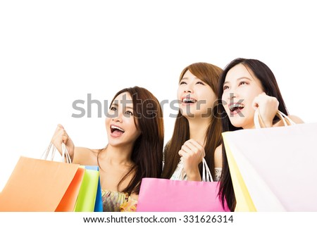 Group of happy young woman with shopping bags looking up - stock photo