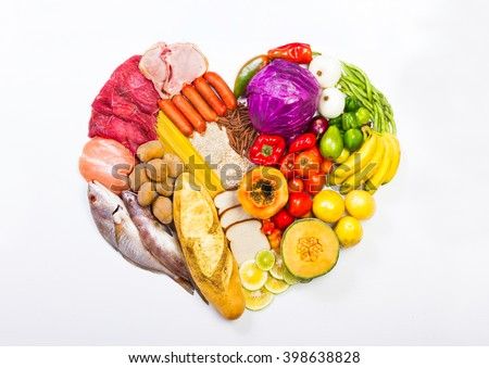 Group of healthy food, the shoot includes protein, carbohydrates, good fats, fruits and vegetables. arranged in the shape of a heart on a plain white surface. - stock photo