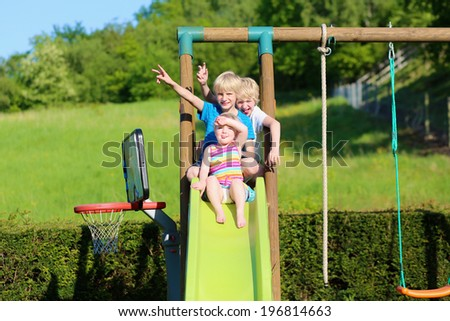 Group of healthy happy kids, two active school boys and funny toddler girl, playing together outdoors on the slide at the backyard of the house in the garden with beautiful field view