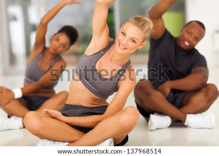 group of healthy people stretching at the gym - stock photo