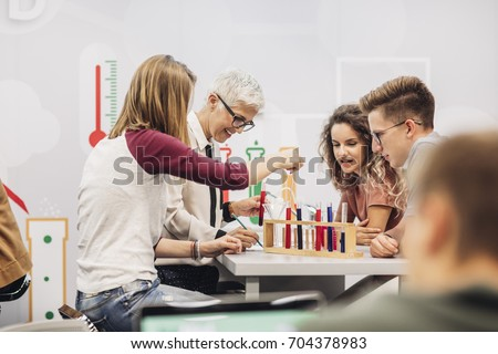 Group of high school students doing science experiments with their chemistry teacher.