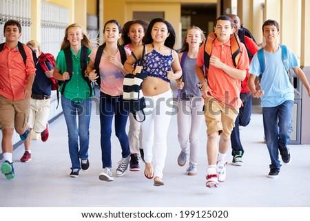 Group Of High School Students Running Along Corridor - stock photo