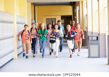 Group Of High School Students Running Along Corridor - stock photo
