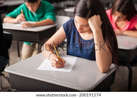 Group of high school students taking a test in a classroom - stock photo