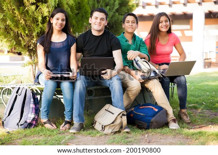 Group of high school students using all kinds of devices while hanging out - stock photo