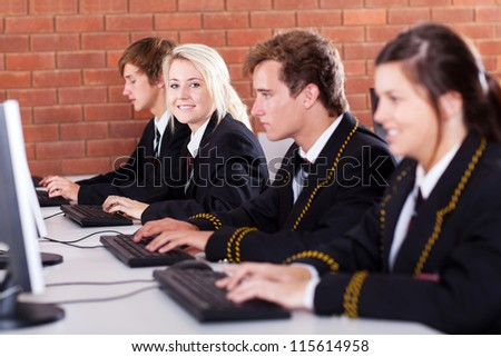 group of high school students using computers in classroom - stock photo