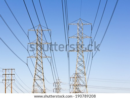 Group of high voltage electrical power transmission line towers. Front view of steel lattice pylon structures, wires, and insulator capacitors. Blue sky background.