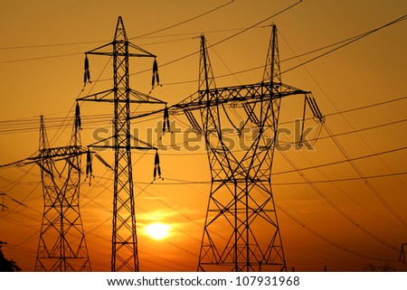 group of high voltage pole against sun - stock photo