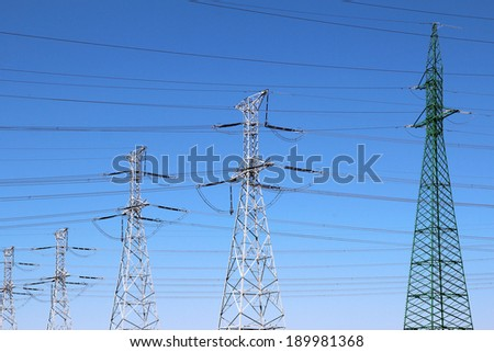 Group of high voltage towers under blue sky - stock photo